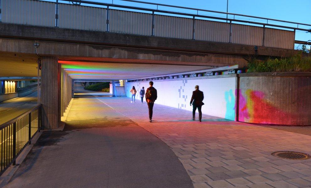 People crossing the illuminated tunnel in Eskilstuna