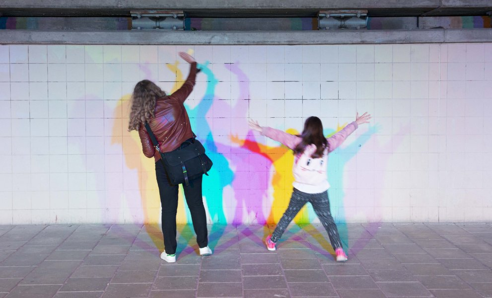 A woman and a girl creating coloured shadow effects on the tunnel wall