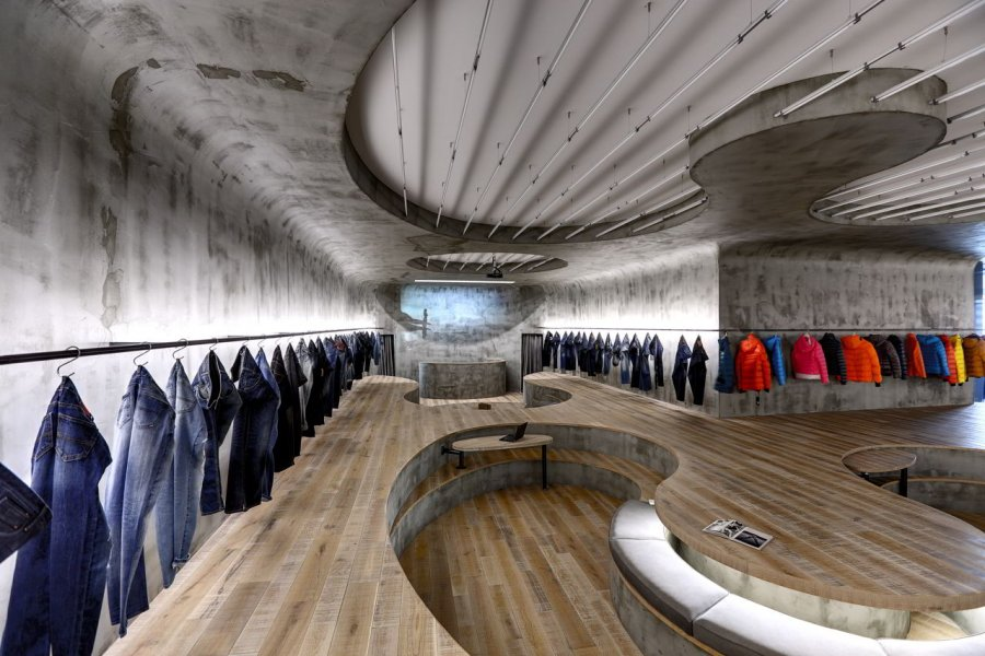 Background lighting to generate visual tension: apparently plain and simple garments are hung up against a backdrop of morbid-looking, grey walls. The lighting applied purposefully underscores – and even enhances – this contrast.