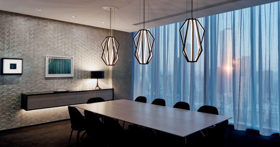 Der Einspruch der maßgeschneiderten, geometrisch auffallenden Pendelleuchte in auserwählten Bereichen des Bürokomplexes ist äußerst wirksam.